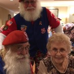 Virginia smiling from ear to ear with these 2 jolly Santas by her side!