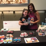Michelina and her mom, Lisa, in front of her table of Floppies!
