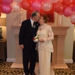 Lester and Regina kissing under the balloon arch.